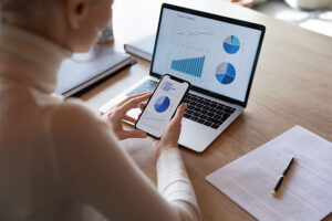 woman looking at digital sales report graphs on her mobile device and laptop